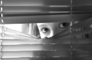 Image of woman looking out of blinds at stalker